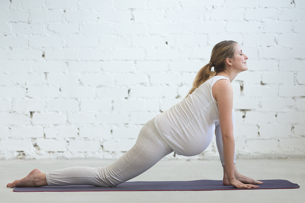 Pregnancy Yoga and Fitness. Young pregnant yoga model working out in loft room with white walls. Pregnant fitness person practicing yoga exercises at home. Prenatal Lizard (dragon yin pose) posture
