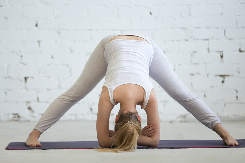 Pregnancy Yoga and Fitness. Young pregnant model working out in loft interior with white walls. Future mom practicing yoga exercises at home. Prasarita Padottanasana. Wide Legged Forward Bend Pose