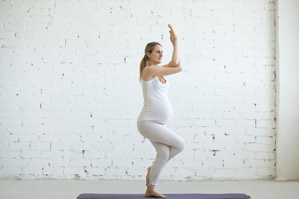 Pregnancy Yoga and Fitness concept. Portrait of beautiful young pregnant yoga model working out indoor. Pregnant happy fitness person enjoying yoga practice at home. Prenatal Eagle Pose, Garudasana